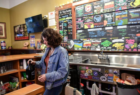 Charla Cross carries a full growler to be sealed at the Growler Haus on North Main Street in Anderson Wednesday, March 18, 2020. State Gov. Henry McMaster declared no dining at restaurants, which has forced many to have pick up orders, including beer in the sealed containers.
