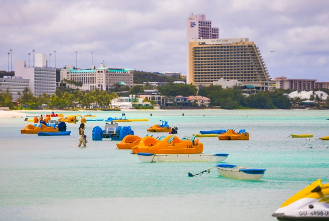 A woman wades in the waters of Tumon Bay near empty watercraft normally utilized by visiting tourists Wednesday.