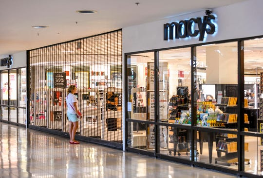 A potential customer speaks to a store employee through the security gate at the entrance to the Macy's store at the Micronesia Mall on Wednesday, March 18, 2020.
