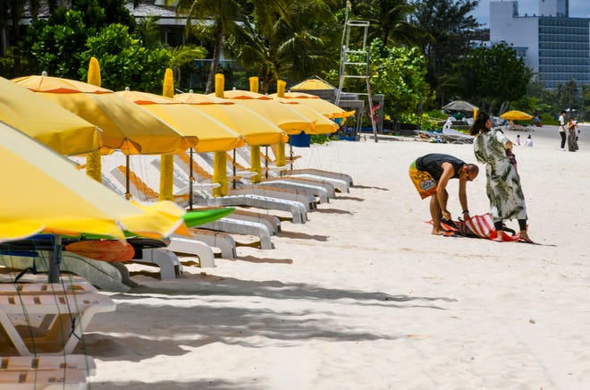 Beach chairs are empty of tourists as a couple with their children prepare to take a cooling dip into the waters of Tumon Bay March 18, 2020.