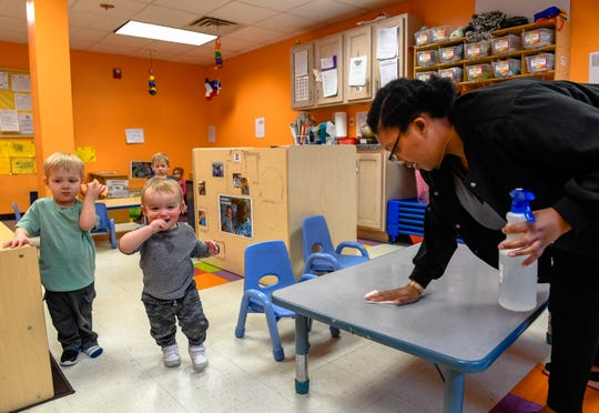 Selena Williams wipes a table down in he one-year-old room at Kidz World daycare as, by executive order issued by the Governor all Kentucky daycare centers will have to close by Friday due to the coronavirus pandemic Wednesday, March 18, 2020.