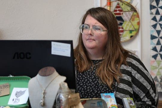 Crimson Tate owner Heather Givans looks at order details on a computer at her Mass. Ave fabric shop.