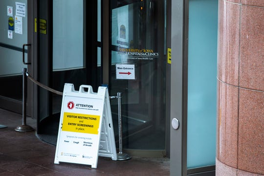 Signs are posted outside entrances listing visitor restrictions and screening while the hospital treats coronavirus patients, Wednesday, March 18, 2020, at University of Iowa Hospitals and Clinics (UIHC) in Iowa City, Iowa.