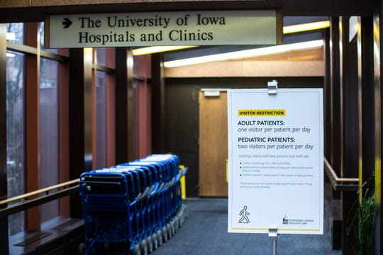 Signs are posted in the skywalk towards an entrance listing new visitor restrictions for patients while the hospital treats coronavirus patients, Wednesday, March 18, 2020, at University of Iowa Hospitals and Clinics (UIHC) in Iowa City, Iowa.