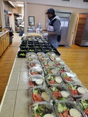 Ashanti Rhody, a member of New Roots' farm-to-school team, preparing meals for students at St. Catherine's Greek Orthodox Church.