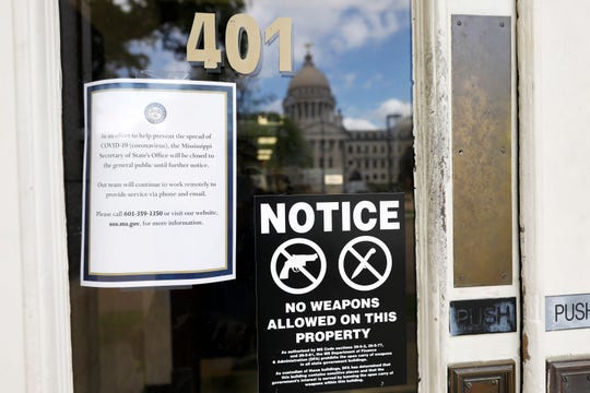 The dome of the state Capitol in Jackson, Miss., is reflected on the front door of the Secretary of State's office, adorned with a closure notice as most state government offices and agencies are closed for an undermined time as a result of the COVID-19 outbreak, Wednesday, March 18, 2020. (AP Photo/Rogelio V. Solis)