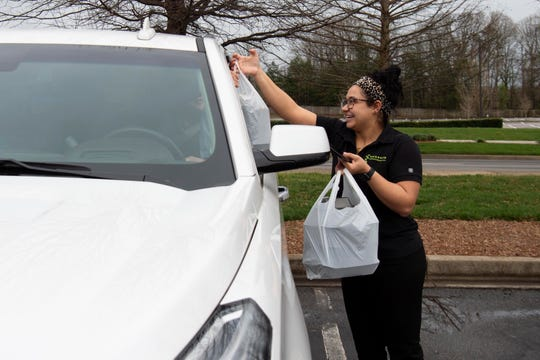 Whitney Donaldson delivers food to a curbside customer at Seasons Innovative Bar & Grill on Tuesday, March 17, 2020. Many restaurants in the area are offering curbside service in response to social distancing.