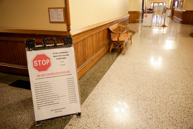 """A sign advising those with """"flu-like"""" symptoms to not enter the Tippecanoe County Courthouse sits inside the first floor, Wednesday, March 18, 2020 in Lafayette"""