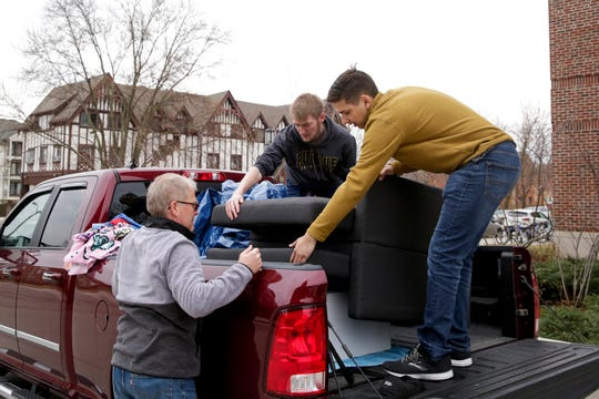 Rick Lahey, left, helps his son, Matt Lahey, center, and Adam Gottwald, right, load the contents of Lahey's daughter's dorm room into three cars, Wednesday, March 18, 2020 at Purdue University in West Lafayette.