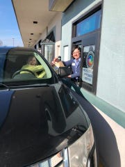 "Rena Aiken, co-owner of Camera Outfitters, hands repaired camera lens to Victoria Rayburn, a Lafayette photographer, at the Market Square business' drive-thru window on Tuesday, March 17, 2020. Camera Outfitters used the drive-thru window, once a part of an Igloo Custard stand, for the first time as the business dealt with ""social distancing"" recommendations tied to the coronavirus pandemic."