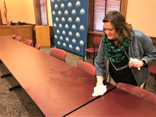 Fairfield County budget officer Staci Knisley wipes down tables and chairs following the county commission's weekly meeting on Tuesday.