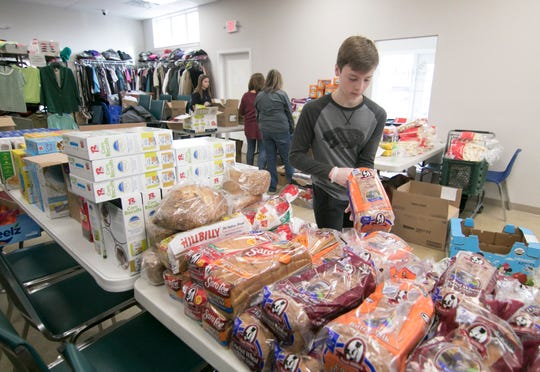 13-year-old Ryan Hemphill volunteers at Bountiful Harvest with his mother Sheryl Hemphill Wednesday, March 18, 2020, packing food for those in need.