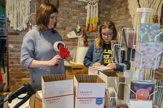 Leslie Delgado is closing her shop in NuLu, Peace of the Earth, during the coronavirus outbreak. Leslie and her daughter, Riley, package online orders to send out Wednesday.
