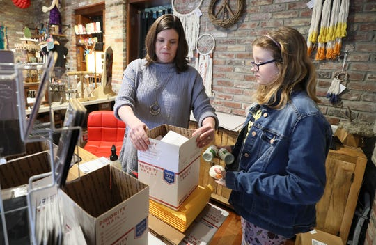 Leslie Delgado is closing her shop in NuLu, Peace of the Earth, during the coronavirus outbreak. Leslie and her daughter, Riley, package online orders to send out on Wednesday.