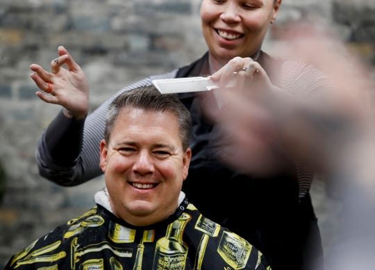 Tara Knight cuts the hair of regular customer Brad Biggers on Wednesday. He doesn't know how long Gov. Andy Beshear will keep the salons closed, so he is getting it cut extra short.