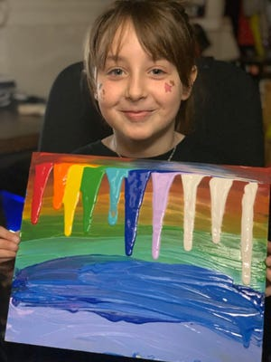 Aubrie Goodall shows off her painted rainbow.