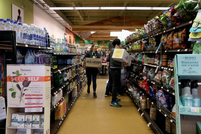 Employees stock the shelves at Rainbow Blossom Natural Food Markets & Wellness Center, 3046 Bardstown Road. The store has introduced special shopping hours for seniors and other customers who are at higher risk of developing the coronavirus.