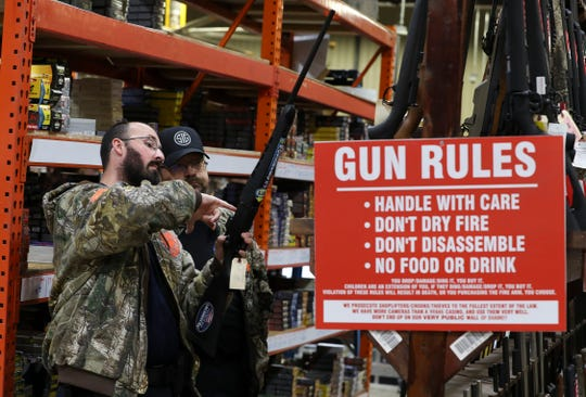 David Downs, left, and Jerry Mills, co-owners of Rocky's Private Protection in Louisville, checked out rifles while shopping at the Kentucky Gun Co. in Bardstown on Wednesday.