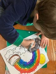 """Jessica Goodall's children work on their rainbows to be displayed in their Germantown home's windows. A community Facebook group called for residents to remember that there is a """"rainbow at the end of the storm"""" amid the COVID-19 pandemic."""