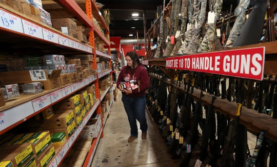 Lauren Skala, 25, of Bardstown, searches for ammunition for hunting at the Kentucky Gun Co. in Bardstown on Wednesday.