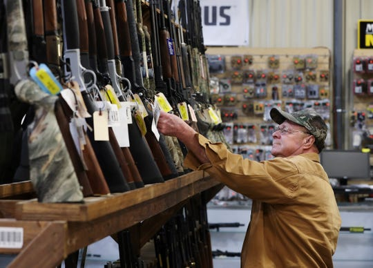 James Clark looks at rifles while browsing at the Kentucky Gun Co. in Bardstown on Wednesday. The store says that sales have spiked amid the coronavirus pandemic.
