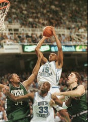 North Carolina forward Vince Carter (15) shoots over Michigan State defenders Andre Huston (34), A.J. Granger (43) and UNC teammate Antawn Jamison (33) during their NCAA East regional semifinal game Thursday, March 19, 1998, at Greensboro Coliseum in Greensboro, North Carolina.