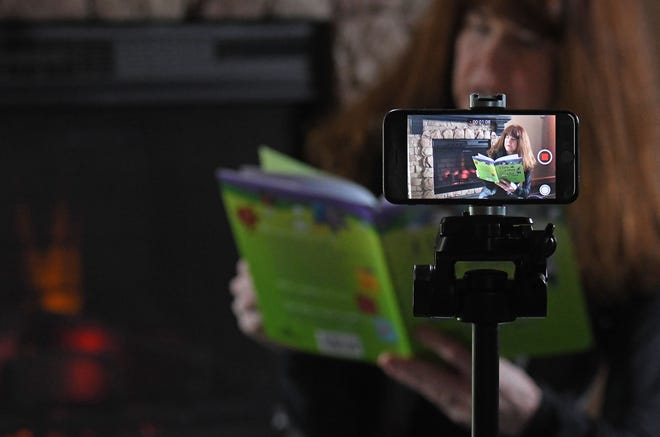 Ann-Marie Molyet, a third grade teacher from Edison Elementary in Ashland, uses a smart phone to record as she reads a book from her Mansfield home. Schools from all over the country are trying to find ways to  educate their students remotely during the Covid-19 pandemic.