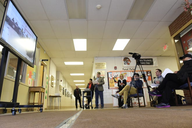The audience of the Mansfield City School Board's regular meeting Tuesday was split, as the door was closed once 10 people filled the meeting room. Everyone else watched via video feed in the hallway outside.