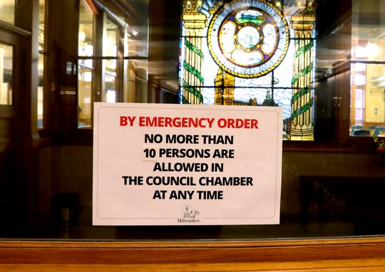 A sign outside the Milwaukee Common Council chambers on March 18 limits the number of people who can gather, a reflection of a state mandate issued in response to the spread of the coronavirus.