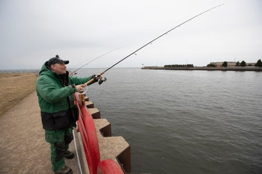 Retired postal worker Jim Dembiec relaxes while fishing near the Milwaukee Harbor entrance Wednesday, March 18, 2020 near the south end of the Summerfest grounds.