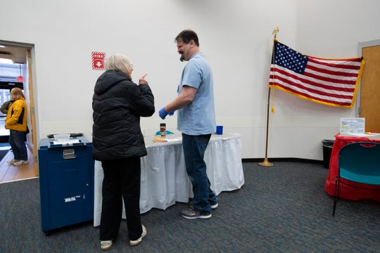 Milwaukee poll worker Patrick Hintz, right, assists a voter with her ballot Wednesday during early voting at the Zablocki branch of the Milwaukee Public Library, 3501 W. Oklahoma Ave.