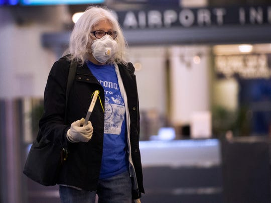 A masked traveler makes her way through the empty concourse to her flight around sunrise Wednesday during what should be one of the busiest times of day at Mitchell International Airport.