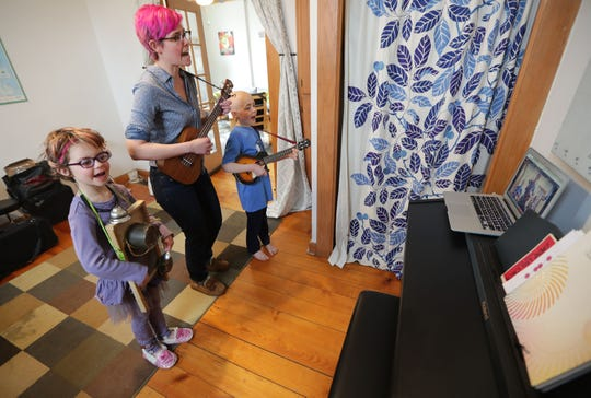 """Milwaukee music teacher Meaghan Heinrich, center, and her children, Margie, 5, on the washboard and Paul, 8, on the ukulele play """"This Land Is Your Land"""" while being recorded live on YouTube at their home in Milwaukee on Wednesday, March 18, 2020. The Milwaukee music teacher, Heinrich started the YouTube series """"Stuck at Home"""", a daily sing-a-long while schools are closed during the COVID-19 crisis."""