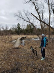 A hiker pauses with her pup on a trail at Lapham Peak in Delafield on March 14, 2020.