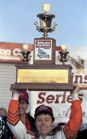 NASCAR driver Alan Kulwicki holds the Winston Cup trophy over his head in victory lane on Nov. 16, 1992, after he won the championship at Atlanta Motor Speedway. Kulwicki edged out Bill Elliott, who won the Hooters 500 race.
