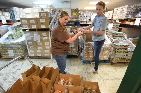 Food Bank of North Central Arkansas Chief Financial Officer Allison Parks, left, and Mountain Home High School senior Jefferson Hodges put together emergency food packs Wednesday for area students.
