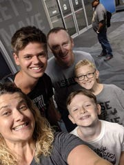 Fabian Burmeister takes a photo with his host family, Maggie (bottom left), Bennett (bottom left), Parker (right) and Tom (top), at the airport.