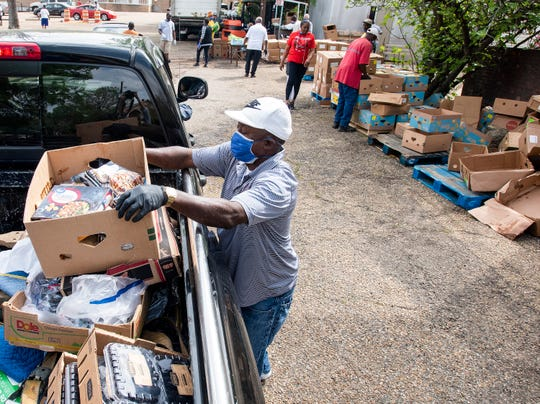 Food is loaded into the back of vehicles as they drive through the Montgomery Rescue Mission food giveaway on Wednesday morning March 18, 2020 at the mission in Montgomery, Ala.
