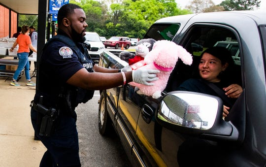 Prattville intermediate School gives out breakfasts and lunches to families of students  that drive up during the scheduled distribution time at the school in Prattville, Ala., on Wednesday March 18, 2020. Prattville police are on hand giving out stuffed animals to students.
