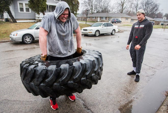 Ball State football player Curtis Blackwell performs tire exercises on the street outside of his apartment with fellow player Dylan Koch after most gyms in the area closed amid coronavirus concerns. Koch and Blackwell said they wanted to avoid Ball State's recreation center to prevent the further spread of the disease.