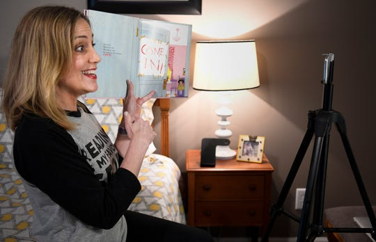 Julie Boggess, a librarian, records a video of herself reading The Big Tidy Up from her home on Wednesday, March 18, 2020 in Franklin, Tenn. Boggess has started her own Facebook group, where she is reading books aloud for all the kids who are out of school during the coronavirus pandemic.