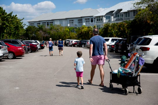 Beach patrons walk back to their cars at the Collier County Barefoot Beach Access on Wednesday, March 18, 2020. Collier County will indefinitely close parking facilities at county beaches starting at sunset on Wednesday in an attempt to slow the spread of COVID-19.