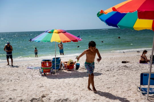 Beachgoers fill the shore at Barefoot Beach in Collier County on Wednesday, March 18, 2020.