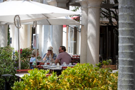 Yvonne Eckman, left has lunch with her daughter-in-low, Jamie Flack Eckman, and her son Richard Eckman, March 18, 2020, at The French outside dining area along 5th Avenue South in Naples.