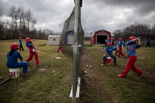 Members of the Lakewood softball team practice for one of the last times before schools would close for at least three weeks and all high school sports were suspended.