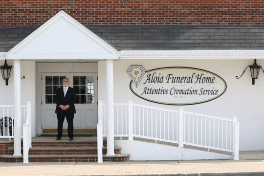 Louis Aloia, owner of Aloia Funeral Home Attentive Cremation Service, poses for a photograph in Garfield.  Aloia said they have removed most of the chairs in their home to practice safe distancing and have also begun to record video of services so that loved ones can watch from the safety of their homes amid the coronavirus outbreak. Wednesday, March 18 2020