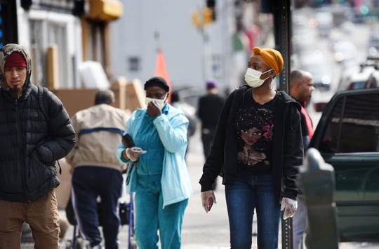 Shoppers wearing masks seen along Main Street in Paterson, Wednesday on 03/18/20.