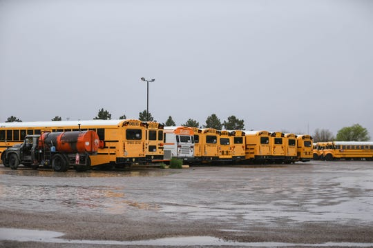 Buses sit empty at an STS of New Mexico lot while schools are closed due to coronavirus concerns in Las Cruces on Wednesday, March 18, 2020.
