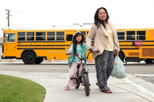 Marianne Alapaid and her daughter, 7 year old Jazne Alapaid walk home after picking up school breakfast and lunch provided by Palm Springs Unified School District in Palm Springs, Calif. on Wednesday, March 18, 2020. Schools closed due to the coronavirus outbreak.
