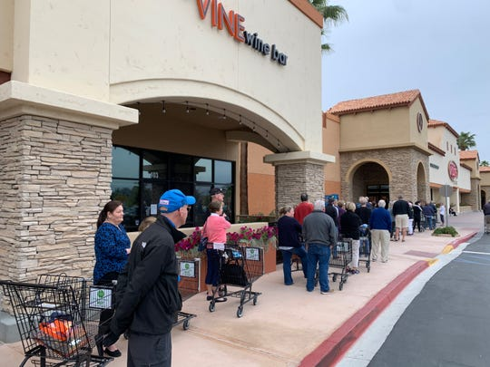 Amid the coronavirus outbreak, the Ralph's grocery store along Cook Street in Palm Desert is only allowing 50 people in the store at a time on a chilly Wednesday morning, March 18, 2020.